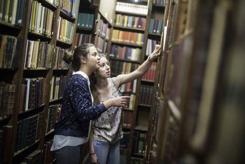 Two female students pick a book from the shelves at a library